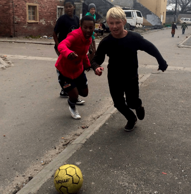 playing soccer with kids in Africa township