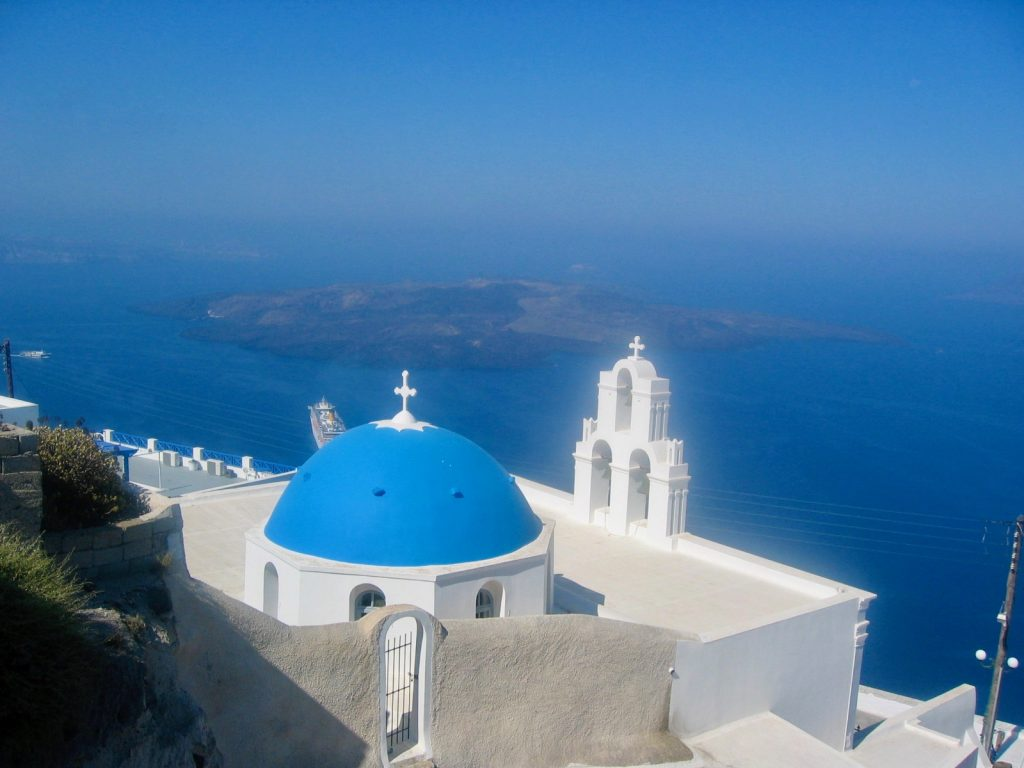 blue domed churches overlooking the Mediterranean sea in Santorini Greece