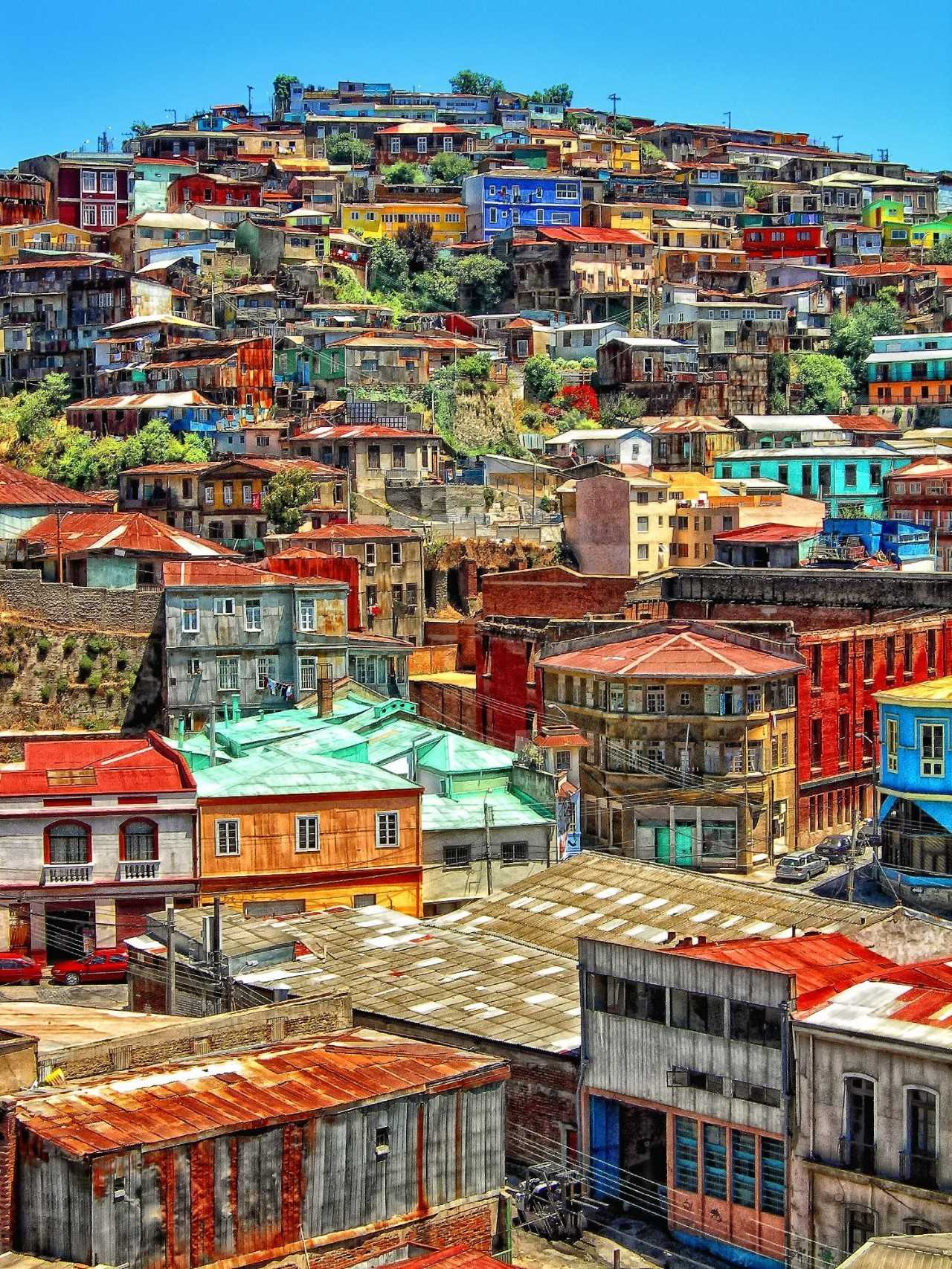 "CITY TRAVEL SOUTH AMERICA GRITTY IS PRETTY: STREET ART IN VALPARAISO | CHILE Posted on March 24, 2017 Vaparaiso Street Art - City View Valparaiso is a bit like San Francisco if the 90's had never ended — think undercuts, paste-ups, and alt-rock bands, with less of the startup douchebaggery. This gritty city by the bay is true to its bohemian roots. There are local events and art exhibits abound, plenty of spots to catch a cheap show, and street art just about everywhere. What more could you want, really? Time in Valparaiso goes down faster than a street dog eats a completo. It is the kind of place you can stay for far too long without other plans to drag you away. Are you planning a visit to Valparaiso? There are plenty of cool things to do in Chile, but be sure to make time to stay and check out the Valparaiso street art. More information on where to find street art + street art tours in Valparaiso below! Valparaiso Street Art Under the Pinochet dictatorship, street art in Chile emerged as a form of protest. It could be done anonymously, so it was one of the safest ways to speak out during quite dangerous times. Decades later, street art is more popular than ever. Local and international artists have developed unique styles and tested them out all over Valpo. You'll find everything from B.R.P, to fauvism, cubism, to wild style decorating the city walls without even having to look too hard.Vaparaiso Street Art - Woman with Sunrise on her Face Almost every building, wall, and storefront is painted in Valpo, with one notable exception – the pitifully white Radio Portales building. Strangely, it's also the most tagged building in Valparaiso. What keeps it so white? Paint jobs. Daily. The rest of Valparaiso, on the other hand, has seemed to adopt the attitude that if you can't beat 'em, join 'em. Businesses and homeowners can either be the local tight ass and fall victim to ugly tags, or they can go ahead and share their wall with a muralist. This culture is what has made the city of Valparaiso into one enormous canvas for spray can art. Vaparaiso Street Art - Taylor in front of a wall Vaparaiso Street Art - Headless Body Vaparaiso Street Art - Homage to ChiloeVaparaiso Street Art -Bus Crossing a Colorful Mural Vaparaiso Street Art - Ally checking out the street art Vaparaiso Street Art - Former ""Happies not Hippies"" Mural Valparaiso Street Art - Man Eating an OctopusVaparaiso Street Art - Hand Grabbing PortholeVaparaiso Street Art - Bored WomanVaparaiso Street Art - Yellow Mural Dig the street art in Valparaiso? Don't forget to follow the artists on Instagram! 1. Man holding a fish bowl by Mr. L 