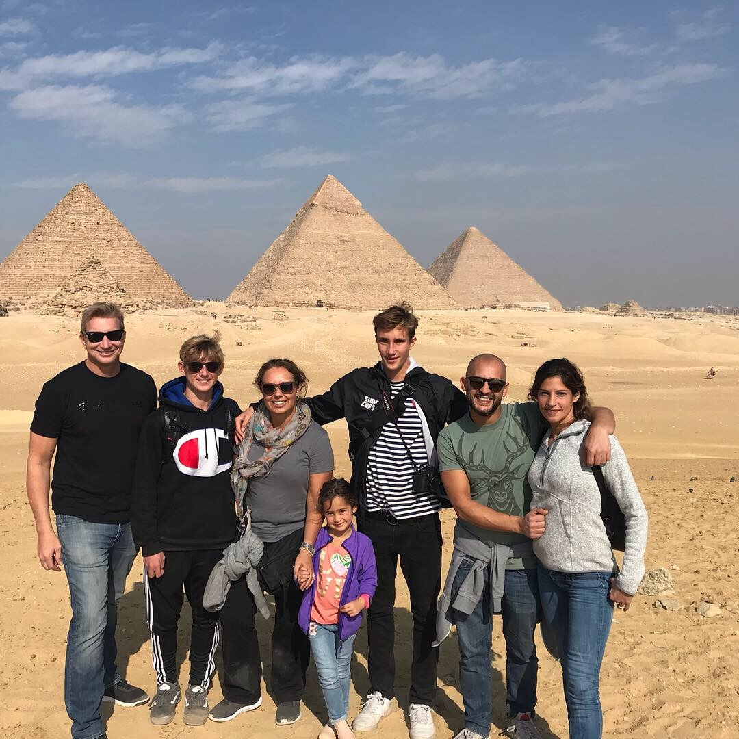 family at pyramids of giza on camels in cairo